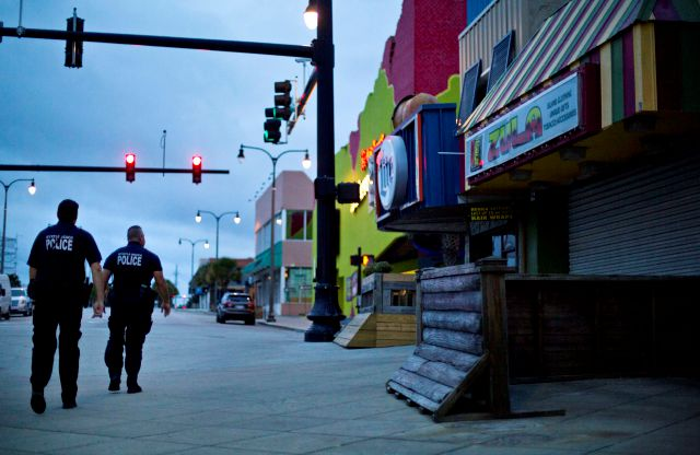 Police patrol past boarded up shops along the boardwalk in Myrtle Beach, S.C., Thursday, Sept. 13, 2018, as Hurricane Florence approaches the east coast. (AP Photo/David Goldman)