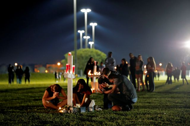People pray around one of seventeen crosses, after a candlelight vigil for the victims of the Wednesday shooting at Marjory Stoneman Douglas High School, in Parkland, Fla., Thursday, Feb. 15, 2018. Nikolas Cruz, a former student, was charged with 17 counts of premeditated murder on Thursday. (AP Photo/Gerald Herbert)