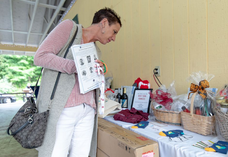 Julie Himes looks through the raffle prizes at a Choose Love fundraiser at the Meriden YMCA Mountain Mist Day Camp on Sept. 5, 2019. The nonprofit, which split the proceeds with Meriden Public Schools, promotes emotional education in youth with the aim of ending school shootings nationally. | Devin Leith-Yessian/Record-Journal