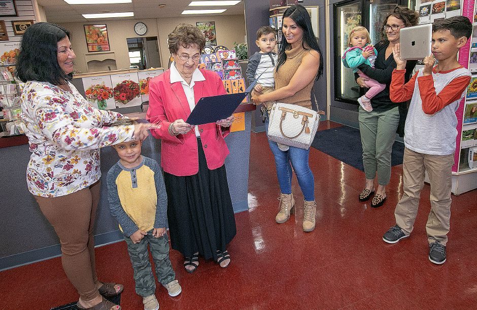 Surrounded by family, Wallingford Flower and Gift Shoppe owner Ann Greco, 92, reads a mayoral proclamation declaring Friday as Ann Greco Day in town, Friday, Oct. 5, 2018. Dave Zajac, Record-Journal