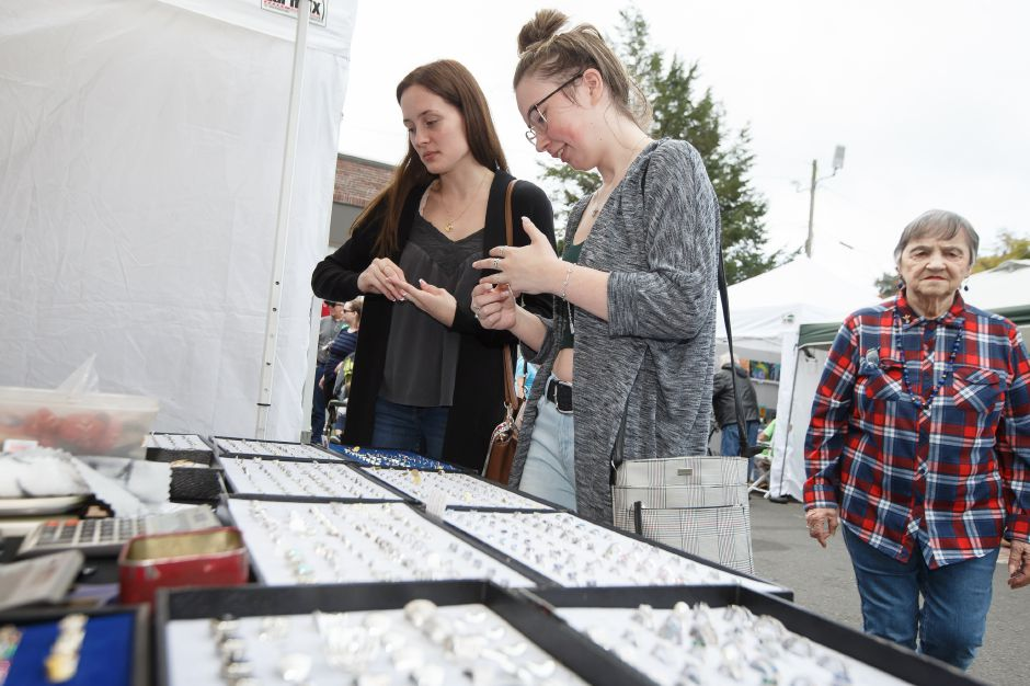 Nicole Chuchro left and Courtney Sillner both of Southington try on jewelry Sunday during the Arts and Crafts show at the Apple Harvest Festival in Southington October 7, 2018 | Justin Weekes / Special to the Record-Journal