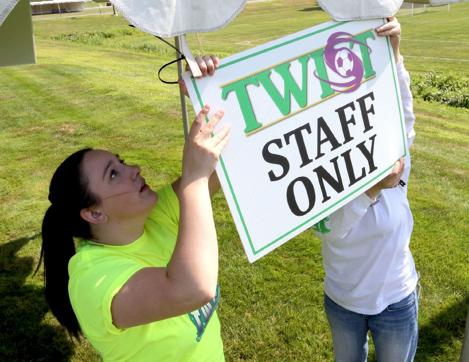 Lizzie Warren, left, and Denise Stowik  hang up a sign at one of the tents at Choate Rosemary Hall as they get ready for the 35th annual TWIST soccer tournament on Friday. Aaron Flaum, Record-Journal