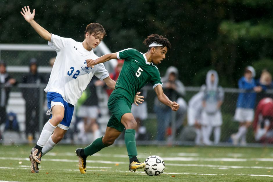 Maloney's Zach Smith gets past a Bristol Eastern defender Monday at Falcon Field in Meriden. The teams tied 1-1.