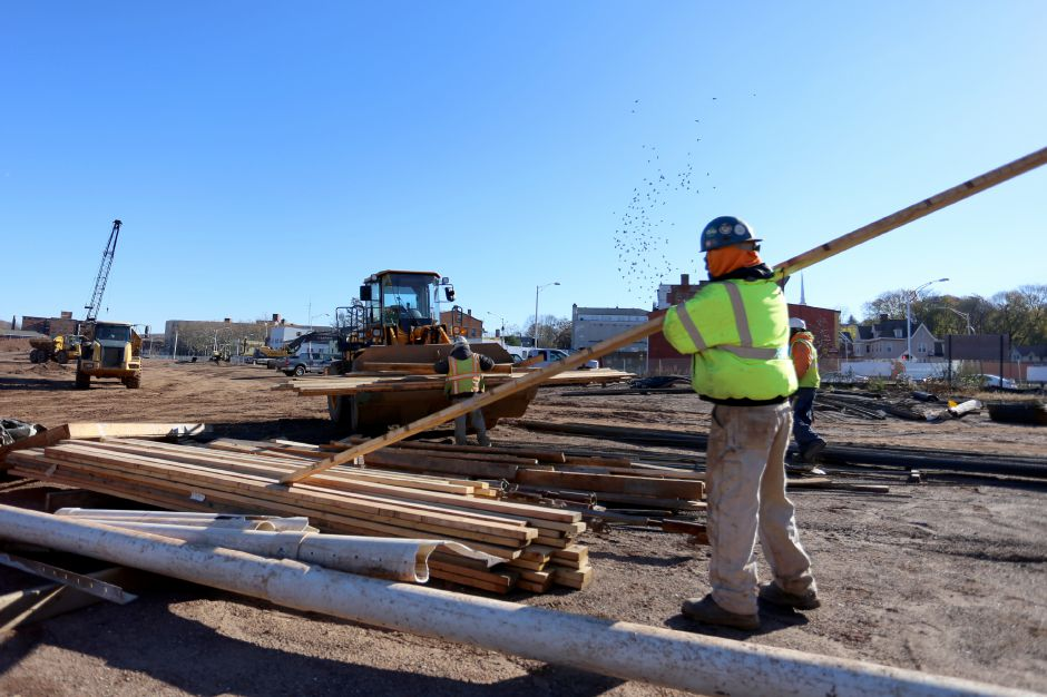 Tyler White, foreground, Marco Ovalle, rear left, and James Yearby, rear right, of LaRosa Construction move lumber at the Meriden Hub site Wednesday Nov. 19, 2014. | Richie Rathsack/Record-Journal