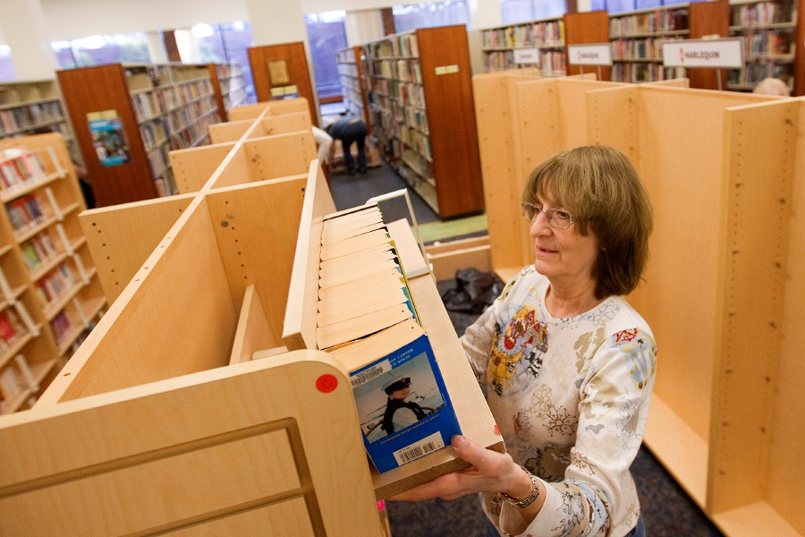Karen Roesler, director of the Meriden Public Library, replaces paperbacks on new shelving as part of renovations there, Thursday, Dec. 10, 2015. The library is installing new lighting, desks and carpeting. | Dave Zajac / Record-Journal