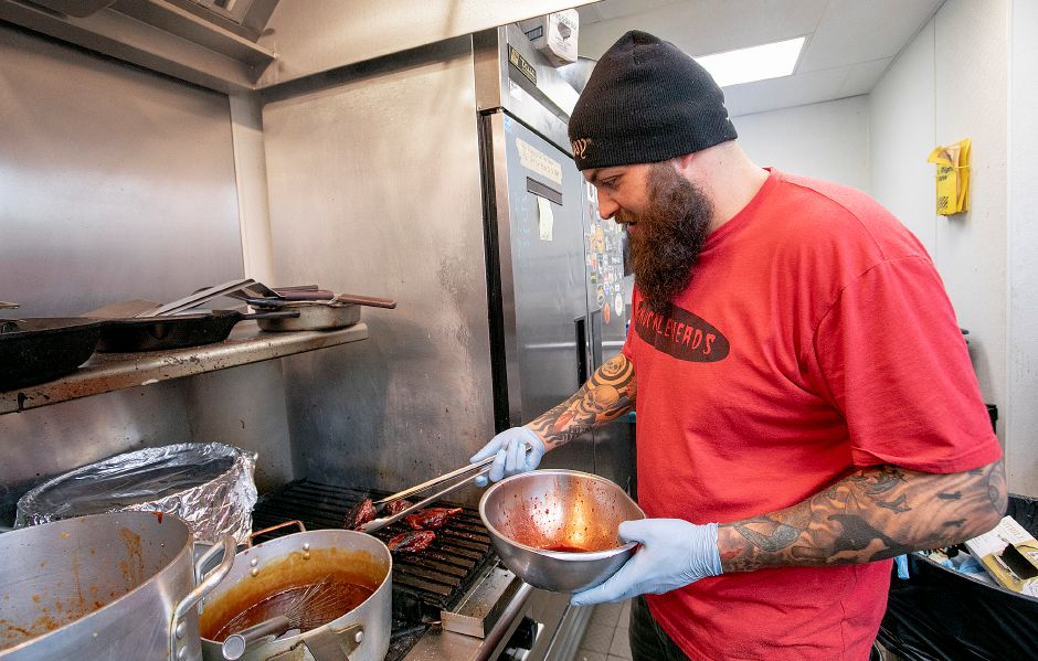 Anthony Morgillo, owner of Knuckleheads, bastes pig wings at the Center Street restaurant Wednesday, Dec. 12, 2018. Dave Zajac, Record-Journal