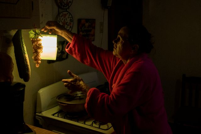 In this July 12, 2018 photo, Marta Bermudez Robles, 66, hangs a lamp in her kitchen in Adjuntas, Puerto Rico, at her home that is still with electricity since Hurricane Irma and Maria. The only power Bermudez and her husband have had for 10 months is courtesy of a neighbor who threw over an extension cord connected to his generator that provides just enough power to light one bulb in the kitchen and another in the living room for a couple hours each day. (AP Photo/Dennis M. Rivera Pichardo)