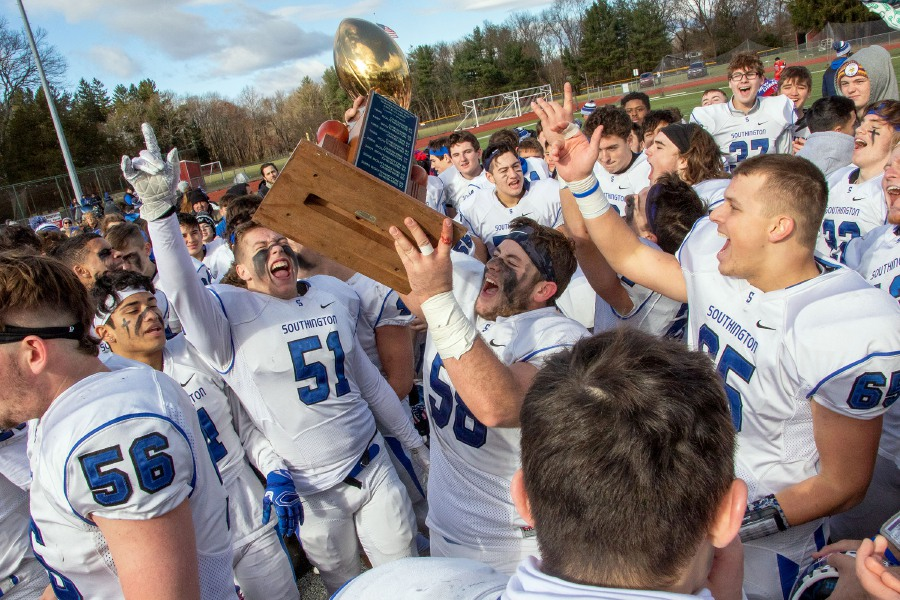 Southington's Jacob Vecchio holds the trophy as he celebrates with his team after the Blue Knights defeated Cheshire in 21-20 in double overtime Thursday at Alumni FIeld in the 24th annual Apple Classic. It was the eighth straight Thanksgiving victory for the Blue Knights. Aaron Flaum, Record-Journal