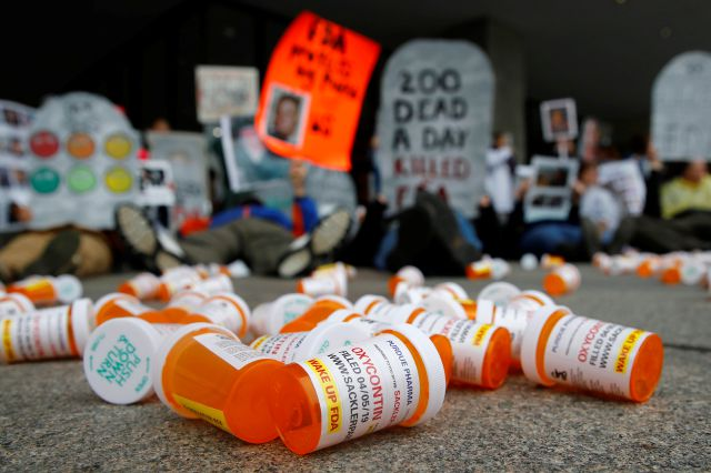 FILE - In this April 5, 2019, file photo, containers depicting OxyContin prescription pill bottles lie on the ground in front of the Department of Health and Human Services