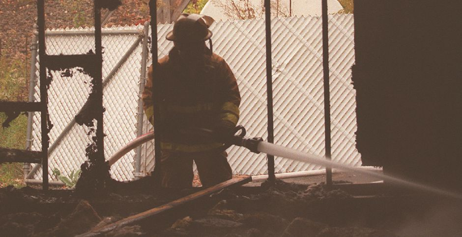 RJ file photo - Southington firefighter Tom Golec hoses down the charred remains of a shed on the old Solvents Recovery Services property on Lazy Lane Oct. 7, 1998.