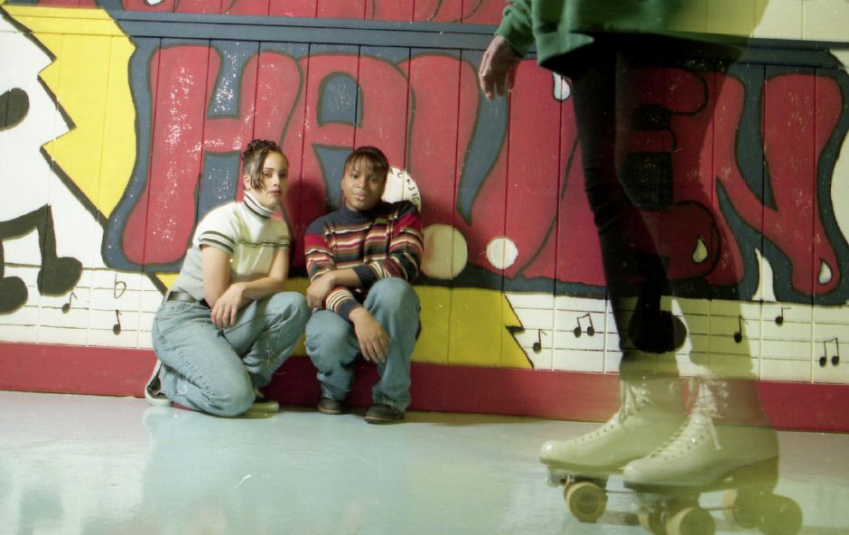 File photo - Maloney High School student Leonora Cajigas, 16, with Kerry-Ann Nesbeth, 14, sits proudly by a mural Cajigas designed and painted at Roller Haven II in Wallingford, Nov. 30, 1995.