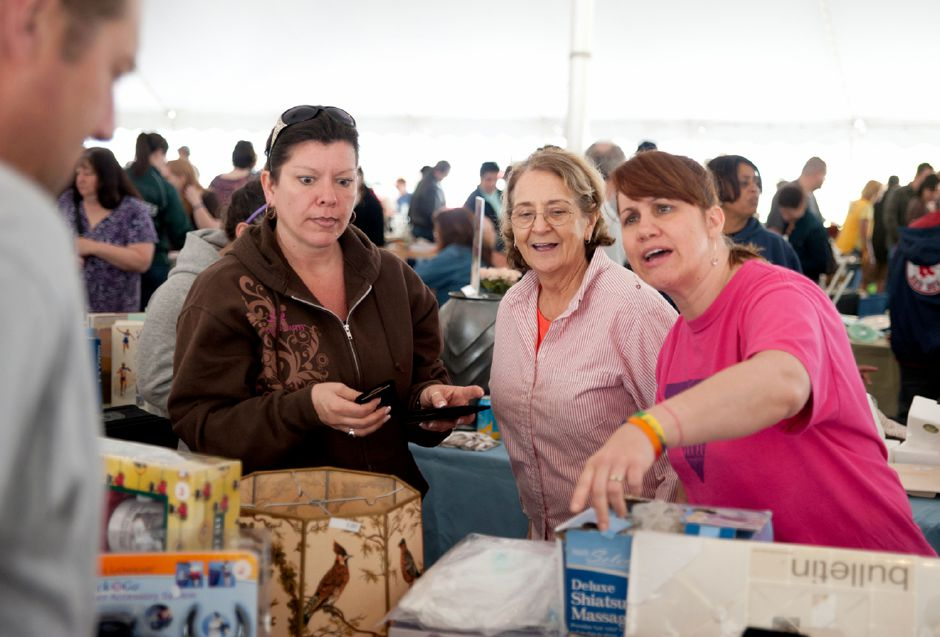 Sue Lazzari (left) of East Hampton, Bernie Levesque (middle) of Cromwell and Kathy Ann Esposito (right) of Northford sell goods at their booth during the Daffodil Festival Tag Sale on Saturday morning.