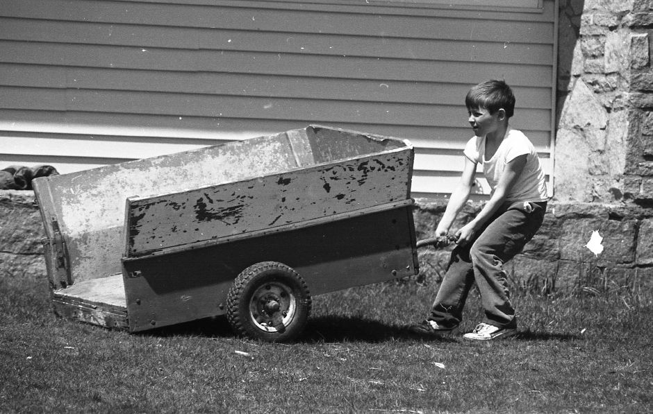 RJ file photo - Adam Cohen, 7, struggles with a cart that attaches to a small garden tractor in front of his Hope Hill Road home, April 1989. Adam was readying the equipment his father would need to mow the lawn when he came home.