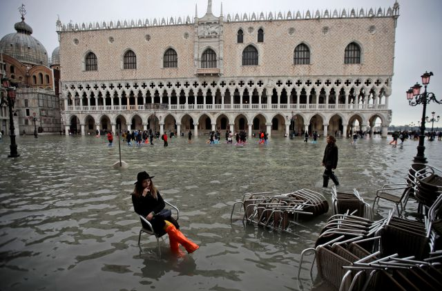 A woman sits in a chair in a flooded St. Mark