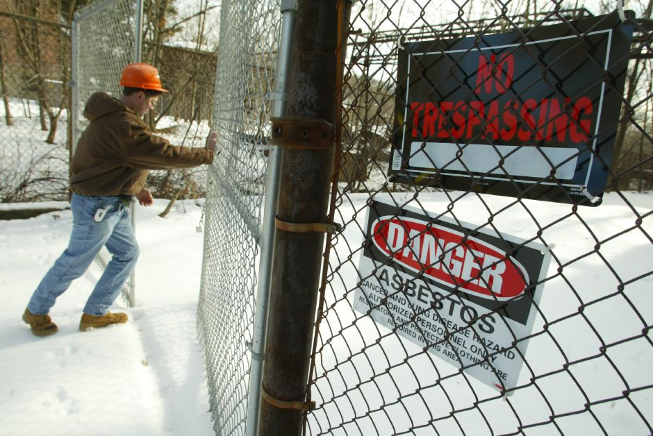 Ray Friegon an environmental analyst for CT D.E.P opens a gate while leading a group of local and state officials on a tour of the defunct Factory H off Cherry Street in Meriden January 10, 2006. (dave zajac photo)