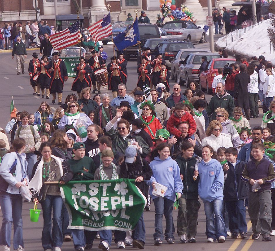 St. Joseph School members carry their banner past the Meriden City Hall building during the St. Patrick