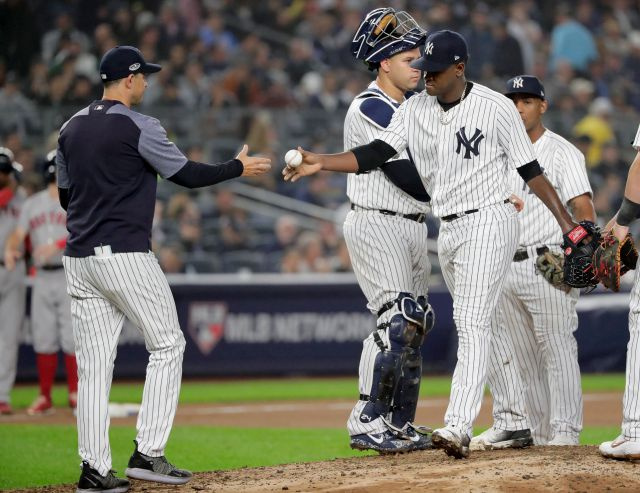 New York Yankees starting pitcher Luis Severino, right, hands the ball to manager Aaron Boone as he leaves the game during the fourth inning of Game 3 of baseball
