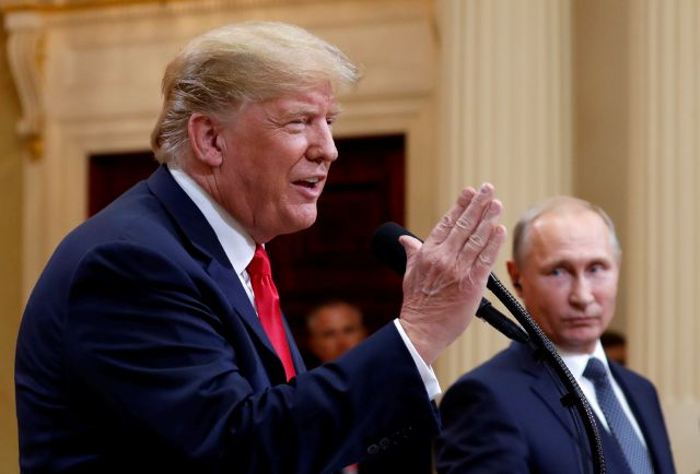 U.S. President Donald Trump,  with Russian President Vladimir Putin at  his side, answers a question during a press conference after their meeting at the Presidential Palace in Helsinki, Finland, on Monday.Associated Press