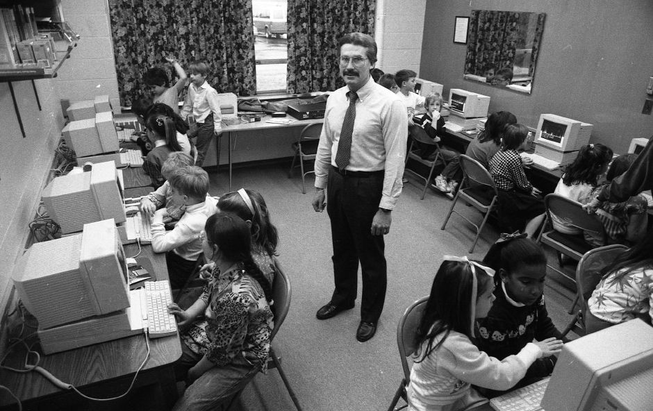 RJ file photo - Thomas Struble, computer coordinator for the Wallingford school system, works with third-graders at Cook Hill School Feb. 21, 1989.