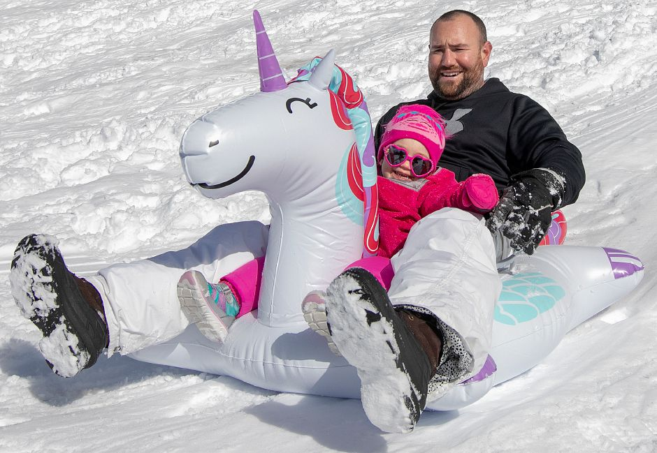 John Patraw and daughter, Leela, 2, of Berlin, ride a unicorn tube down a snow covered hill at Panthorn Park in Southington, Mon., Mar. 4, 2019. An overnight storm left about 10 inches of snow in the area. For more photos see myrecordjournal.com.