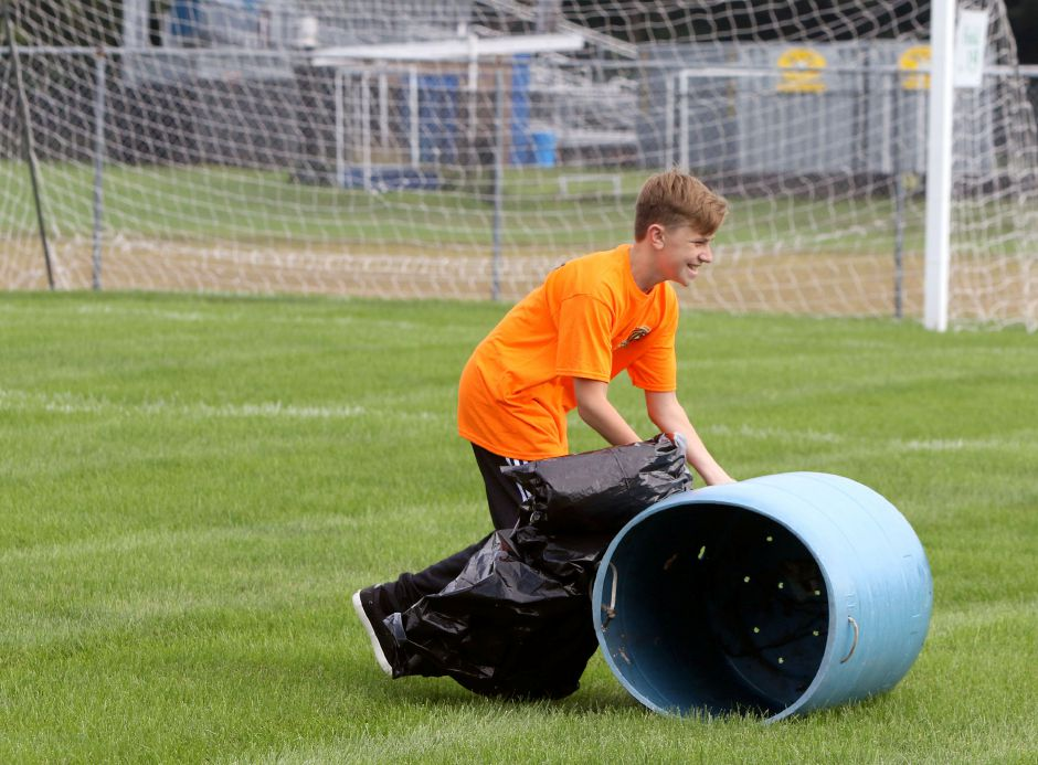Talan Burr, 13, moves one of the garbage cans across the field at Lyman Hall as organizers get ready for the  TWIST soccer tournament. Aaron Flaum, Record-Journal