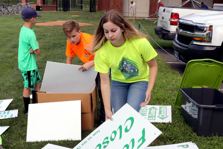 Talan Burr, 13, (orange shirt) and Isabella Stowik, 18, both from Wallingford, sort through signs Friday at Choate Rosemary Hall as they help the Wallingford Youth Soccer League prepare for the 35th annual TWIST soccer tournament, which plays this weekend on various fields across Wallingford.  Aaron Flaum, Record-Journal Staff