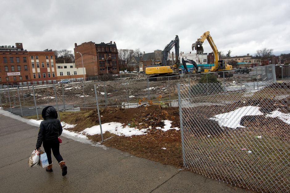 A woman walks by new fencing being installed around the HUB site as excavators continue demolition of the former bank at the corner of E. Main and State Streets, Monday, January 6, 2014. | Dave Zajac / Record-Journal