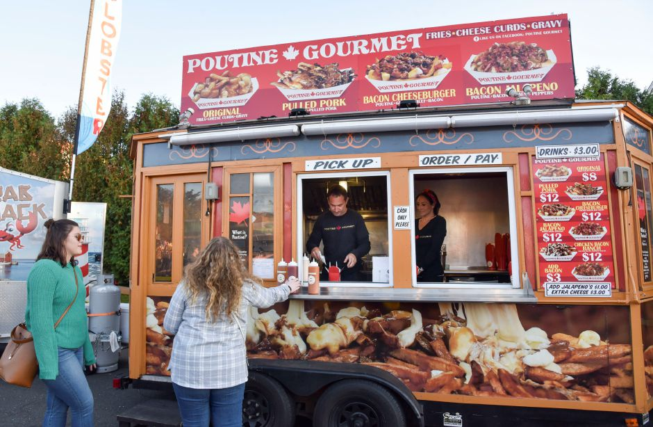 Kris Barletta serves poutine to a customer from his Poutine Gourmet food truck at the Apple Harvest Festival in Southington, on Oct. 4, 2019. | Bailey Wright, Record-Journal