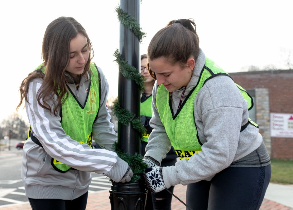 Juliana, left, and Mikayla Mancini, a freshman and a senior at Berlin High School, adjust decorations put up through the school