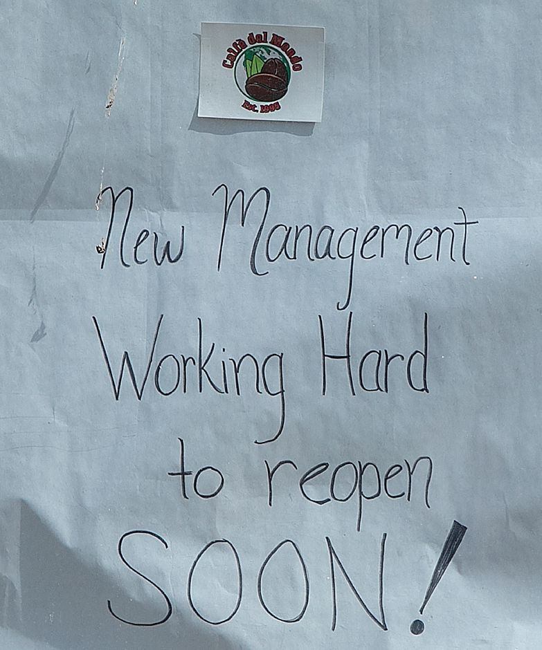 "A sign in the window of Caffe Del Mondo reads ""New Management Working Hard to reopen SOON!"""
