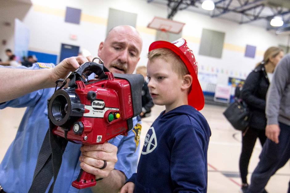 Lt. John Myska, of the Plainville Fire Department, shows Logan Nadeau, 5, of Bristol, a thermal imaging device at the 2018 Plainville Family Fest.