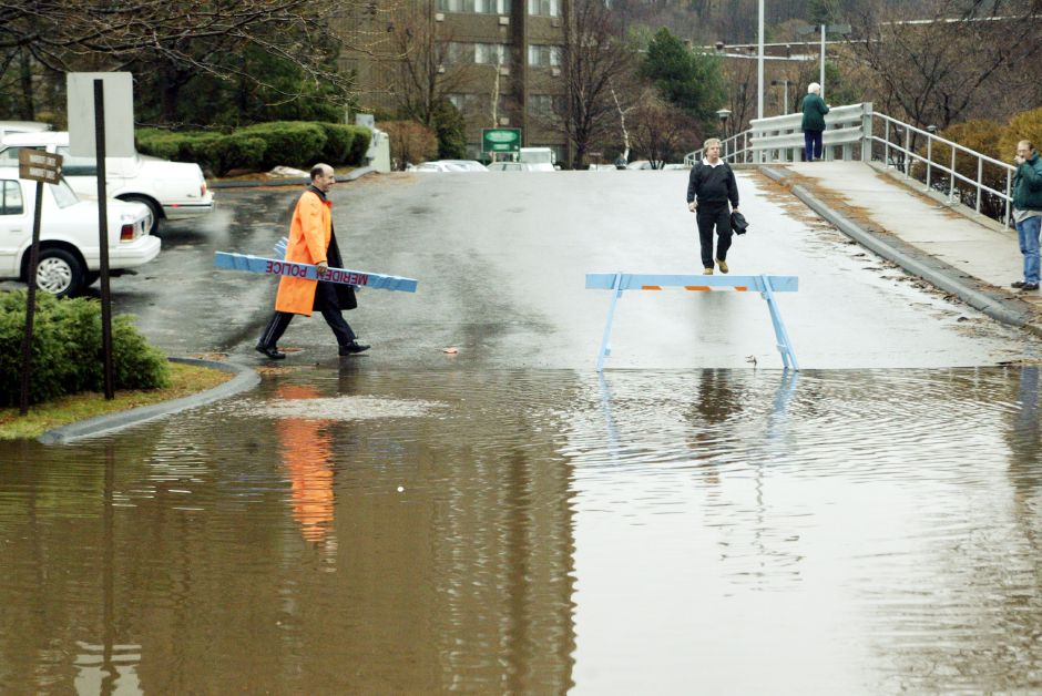 Meriden Community Police Officer Daren McKay sets out some barricades from the Harbor Towers driveway onto Hanover St. Fri., Dec. 20 due to flooding.