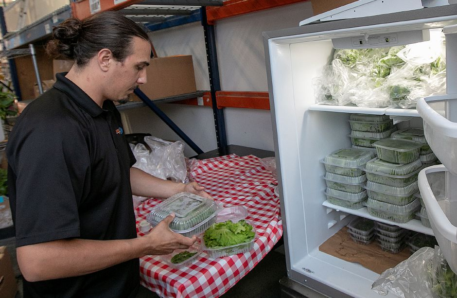 Eric Francis, Chief Operating Officer of Trifecta Ecosystems, shows harvested leafy greens stocked in a refrigerator at the business on Pratt Street in Meriden, Monday, July 23, 2018. The company recently received a 500,000 investment from the South Central Regional Water Authority to help expand its farming and education operations. Dave Zajac, Record-Journal