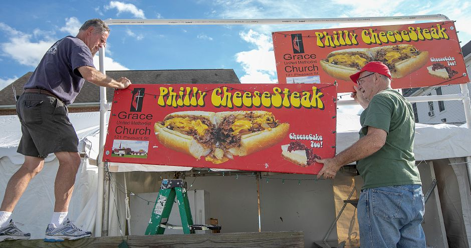 Grace United Methodist Church members Bill Leonard, left, and Dick Spencer, hang philly cheesesteak signs on the church