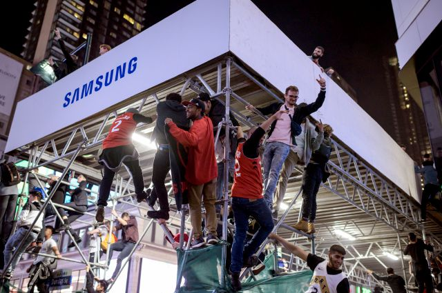 Toronto Raptors supporters climb a scaffold as fans celebrate in the streets after the Raptors defeated the Golden State Warriors during Game 6 NBA Finals to win the NBA Championship, in Toronto on Thursday, June 13, 2019. (Christopher Katsarov/The Canadian Press via AP)