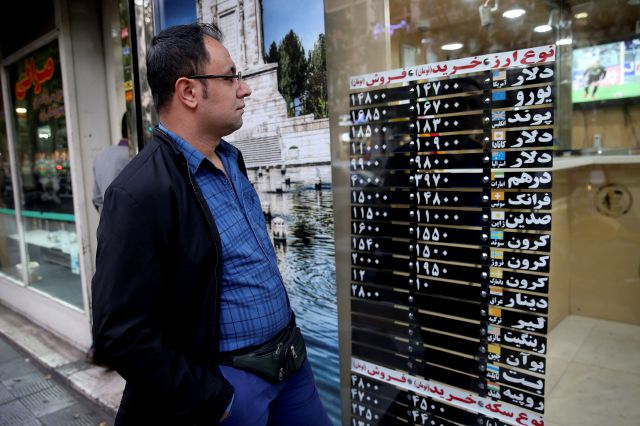 "An Iranian checks various currency rates at an exchange shop window in downtown Tehran, Iran, Monday, Nov. 5, 2018. Iran greeted the re-imposition of U.S. sanctions on Monday with air defense drills and a statement from President Hassan Rouhani that the nation faces a ""war situation,"" raising Mideast tensions as America"