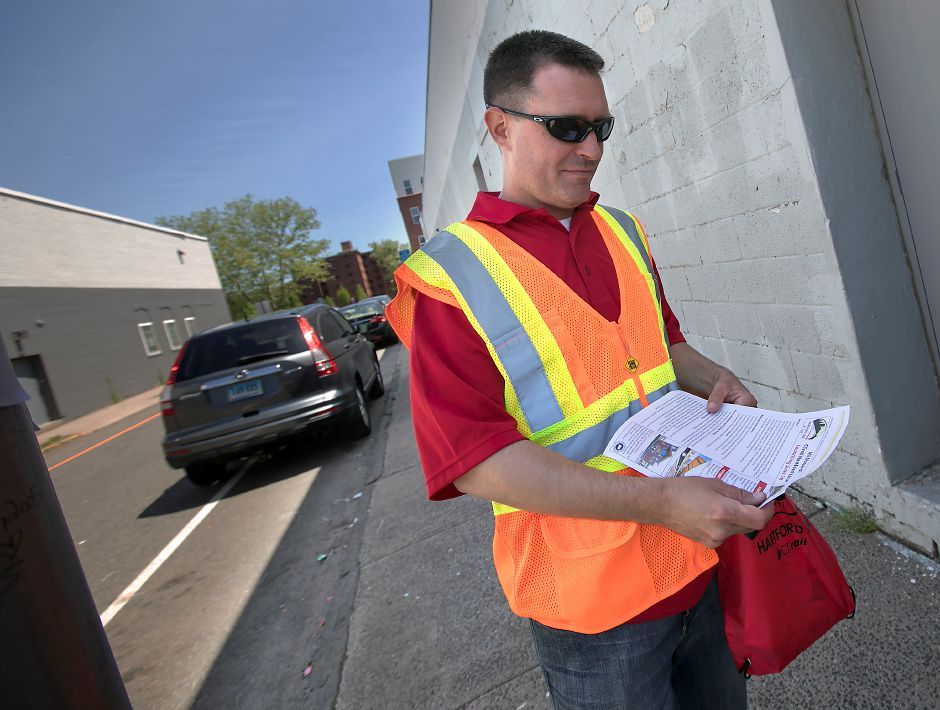 Shawn Callaghan, top, an Operation Lifesaver safety ambassador, hands out literature Wednesday regarding the CTrail Hartford Line at the Cross Street rail crossing in Meriden. Pedestrians, including the unidentified man, left, and Jeffrey Burts, of Meriden, above, are being informed of the new CTrail Hartford Line schedule.       Photos by Dave Zajac, Record-Journal