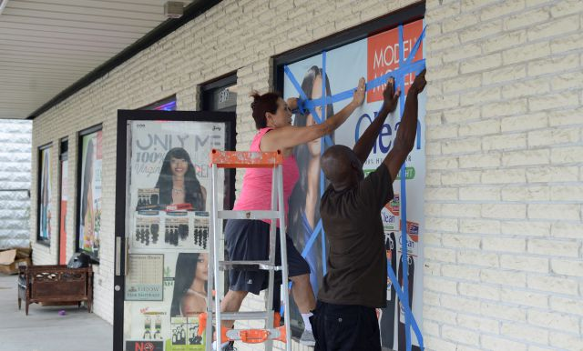 Sam Kim and Donald Walker tape up the windows Wednesday, Sept. 12, 2018 at Sam