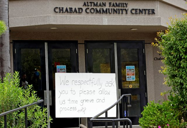 "FILE - In this April 29, 2019 file photo, A sign asks for time to grieve at the Chabad of Poway synagogue in Poway, Calif. The gunman who attacked the synagogue last week fired his semi-automatic rifle at Passover worshippers after walking through the front entrance that synagogue leaders identified last year as needing improved security. The synagogue applied for a federal grant to better protect that area. The money, 150,000, was approved in September but only arrived in late March. ""Obviously we did not have a chance to start using the funds yet,"" Rabbi Scimcha Backman told The Associated Press.(AP Photo/Gregory Bull, File)"
