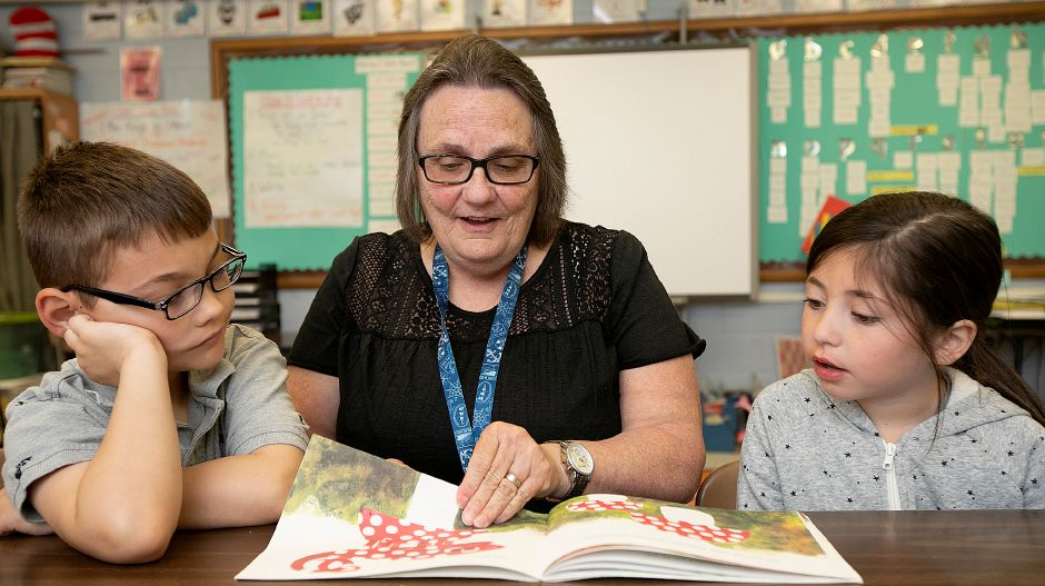 Paraeducator Connie Sperlazza reads a book with first-grade students, Edward Opalacz, 7, and Gianna Valentino, 6, at E.C. Stevens Elementary School in Wallingford, Thurs., May 23, 2019. Sperlazza was recently named the Wallingford Public Schools Paraeducator of the Year for 2019-2020. Dave Zajac, Record-Journal