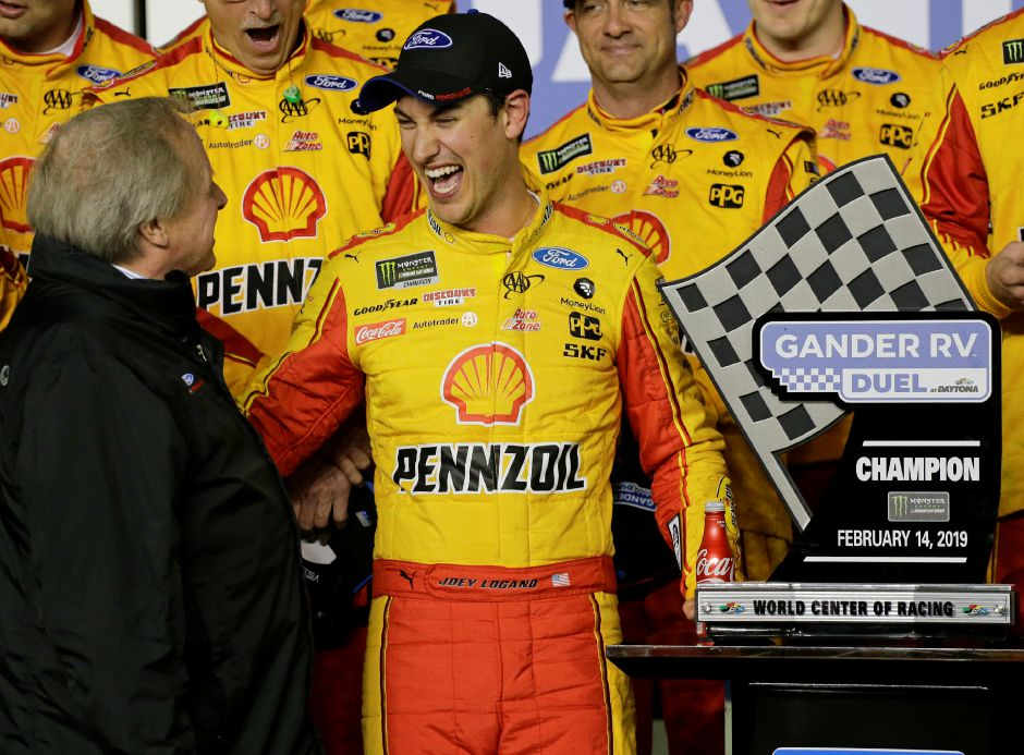 Edsel Ford II, left, congratulates Joey Logano, center, after he won the second of two qualifying auto races for the NASCAR Daytona 500 at Daytona International Speedway, Thursday, Feb. 14, 2019, in Daytona Beach, Fla. (AP Photo/Terry Renna)