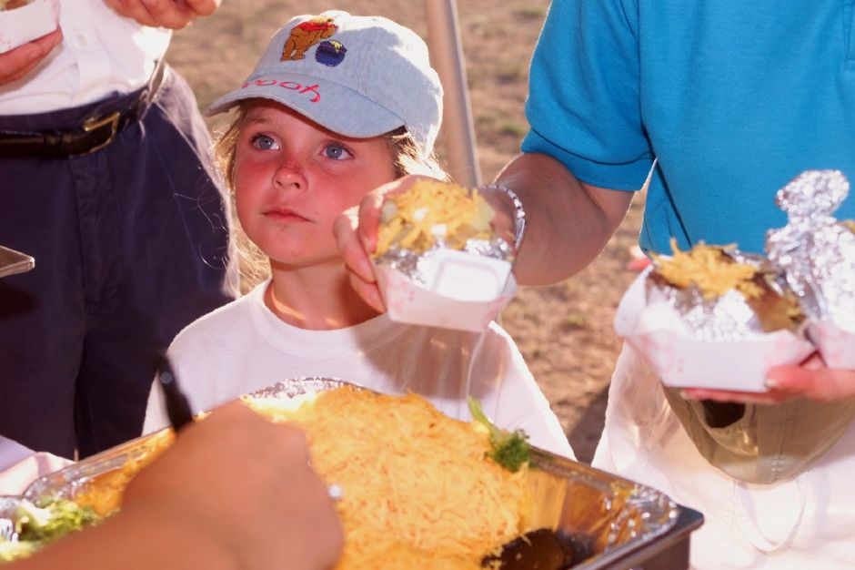 Nina Bagwell, 5 and a half, watches as Parks and Rec. camp councilor Meaghan Damato, left, adds toppings to baked potatoes that her mother holds at Dolittle Park Wed., july 28 1999.