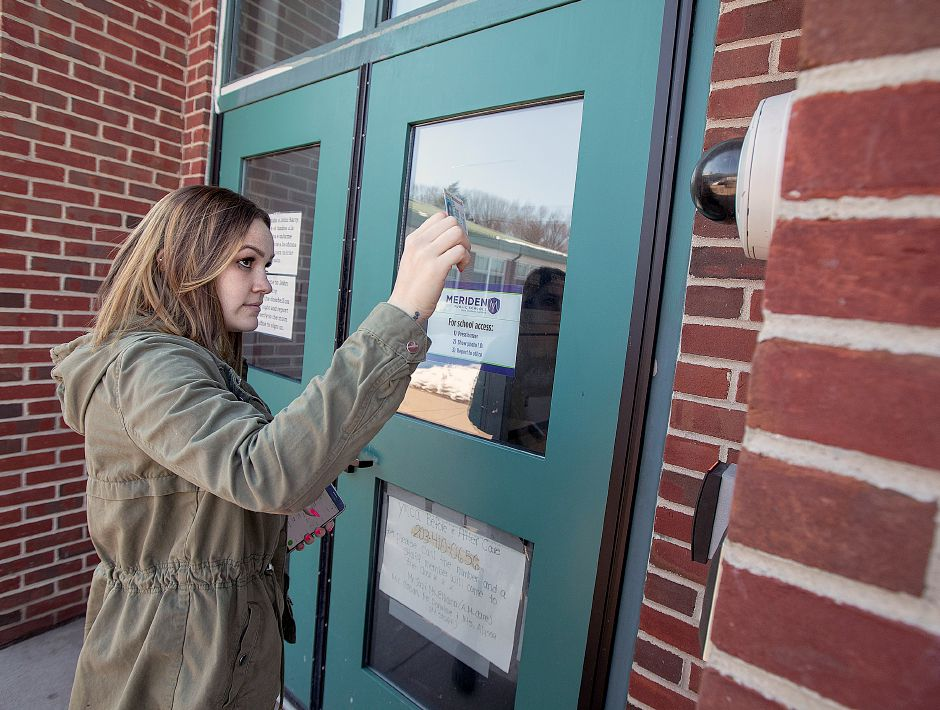 Janet Villafane, of Meriden, shows identification before entering John Barry Elementary School in Meriden, Mon., Mar. 11, 2019. Dave Zajac, Record-Journal