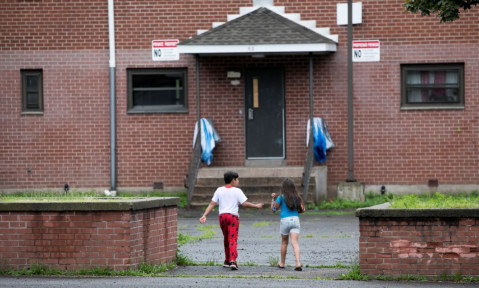 Jordan Agosto, 9, and sister, Luzmari, 8, walk back to their residence at the Mills Memorial Apartments in Meriden, Friday, July 14, 2017. | Dave Zajac, Record-Journal