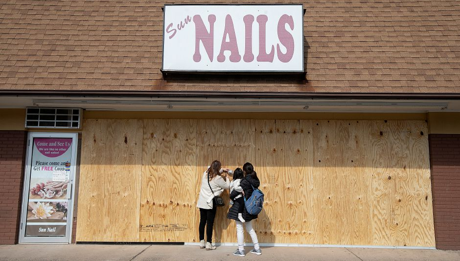 jenieJenny Rhee, left, owner of Sun Nails Salon, and a relative, who declined to be identified, post a sign to the boarded up business at 826 E. Center St., Wallingford, Thurs., Mar. 14, 2019. A vehicle crashed into the nail salon Thursday morning, significantly damaging the storefront. Dave Zajac, Record-Journal