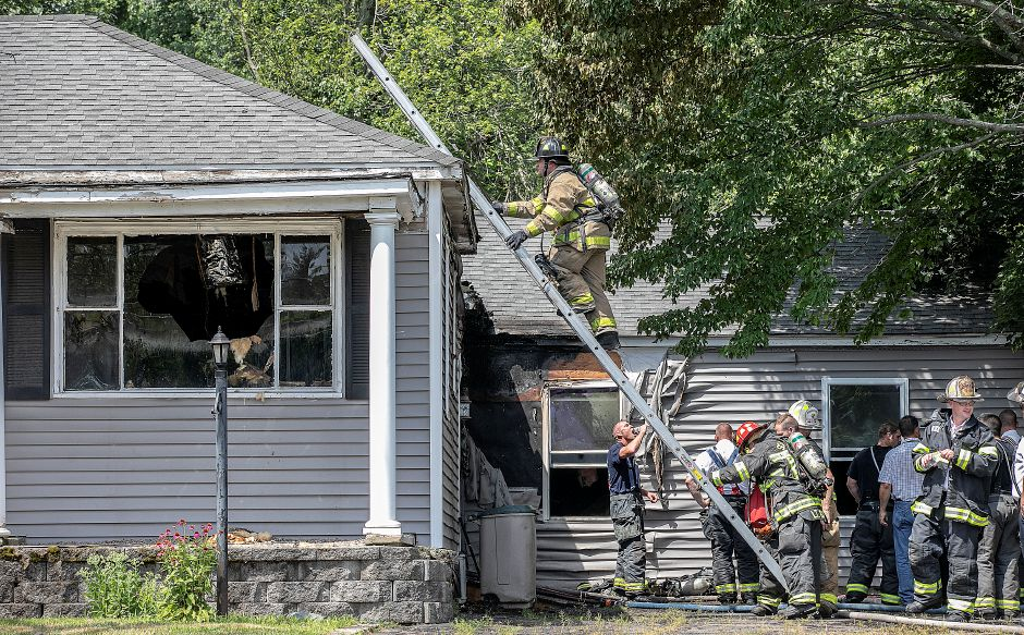 A Southington firefighter climbs to the roof of a residence damaged by a blaze at 354 Clark St. in Southington, Wed., July 17, 2019. No one was home at the time and no injuries were reported. Mutual aid was requested and Meriden and Cheshire crews responded to the scene. Dave Zajac, Record-Journal