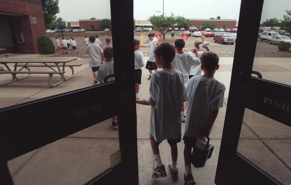 Kyle Mischke, 8, left, and Douglas Biancur, 8, right, walk out the doors together at The Wallingford Park and Recreation Center toward the parking lot where they practice basketball, July 1999.