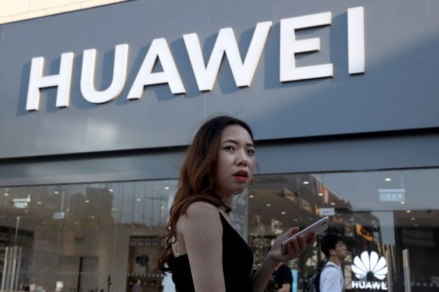 A woman uses a smartphone outside a Huawei store in Beijing Monday, May 20, 2019. Google is assuring users of Huawei smartphones the American company