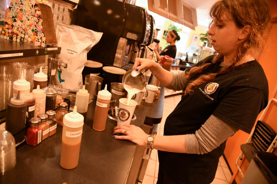 Cheshire Coffee manager Alyssa Trifone makes a drink on Wednesday. The coffeehouse recently added fall-themed drinks and food items back to their menu. Bailey Wright, Record-Journal