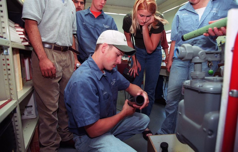 RJ file photo - Joe Lovejoy holds a piece of piping that connects to a standard gas meter he is learning about during a tour of Wilcox Technical students at Yankee Gas in Meriden June 15, 1999. Behind him student Laura Anderson watches. The students spent most of the day touring the building.